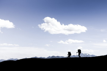 Silhouettes of two hikers walking along the cliff edge