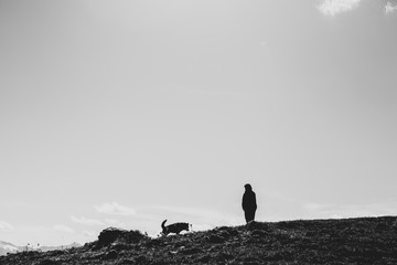 Woman and dog silhouettes on a cliff edge