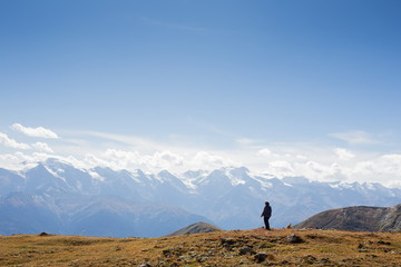 Woman standing on a cliff edge high up in the mountains