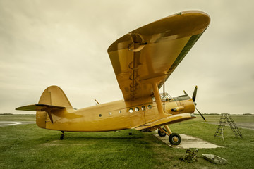 historical airplane gets service on a meadow