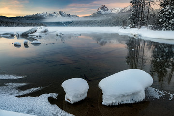 Sunrise over Idaho mountain Redfish Lake with snow and sunrise reflection