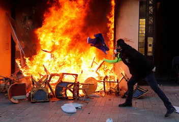 """Protester throws an EU flag into the fire of a burning shop during a demonstration by the """"yellow vests"""" movement in Paris"""