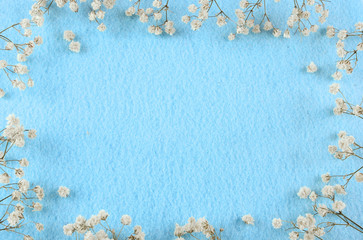 Blue felt background and babies breath border with copy space. Great for wedding, anniversary, mother's day or birthday. Feminine vibe.