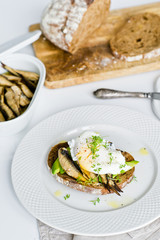 Toast of black bread with avocado, poached egg and sprats. White background, side view.