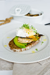 Toast with avocado, poached egg and sprats. White background, side view, close-up.