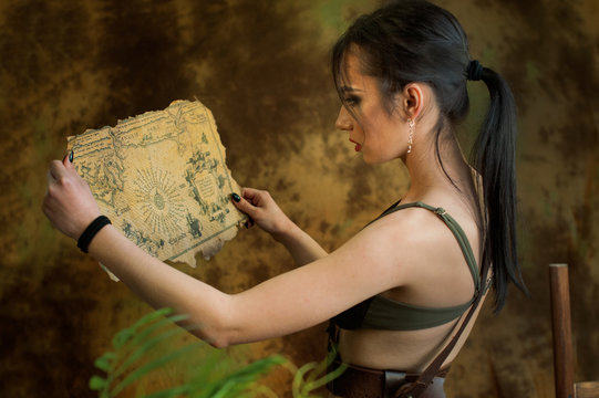 A young girl dressed up as a cosplay woman in jungle discovery old map with treasures