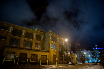 Fotomurales - Industrial winter street city night scene with vintage factory warehouses and the Chicago skyline