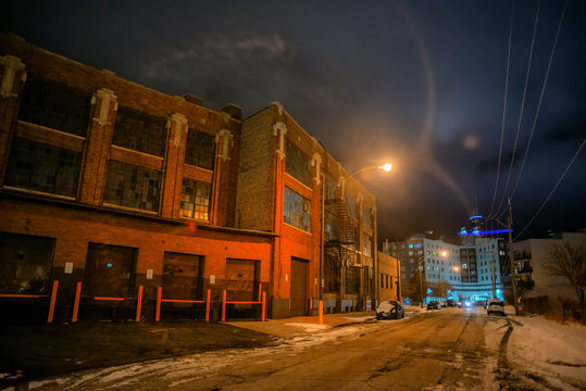 Industrial winter street city night scene with vintage factory warehouses and the Chicago skyline