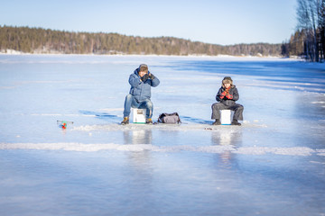 Father and son at the winter fishing on frozen lake