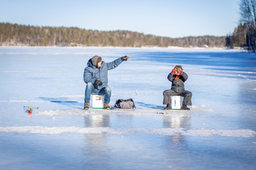 Father and son at winter fishing on frozen lake