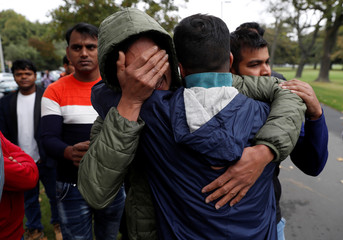 Relatives of a member of the Bangladeshi community wait for news at a community centre in Christchurch