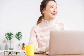 部屋でラップトップコンピューターを見るシニア女性
