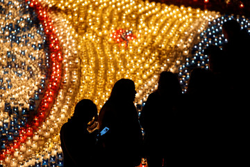 A visitor uses a mobile phone while walking near a display of candles during the Festival of Lights Cittadella, in the medieval citadel in Victoria, on the island of Gozo