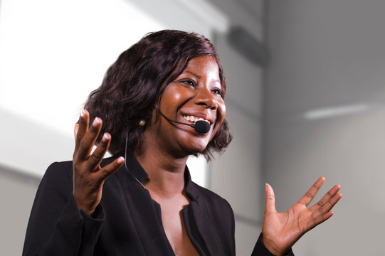 young attractive and confident black African American business woman with headset speaking in auditorium at corporate training event or seminar giving motivation conference