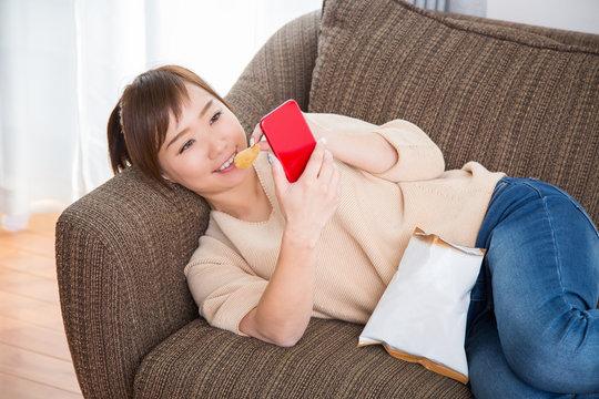 ソファでポテチを食べながらスマホを見る女性(笑顔)