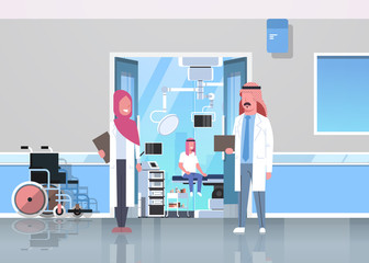 arab doctors discussing in hospital corridor with wheelchair open door to surgery room arabic man sitting operating table modern clinic interior flat full length horizontal