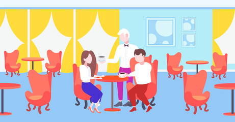 waiter serving coffee to visitors couple sitting at restaurant table modern cafe interior staff hospitality concept horizontal flat full length