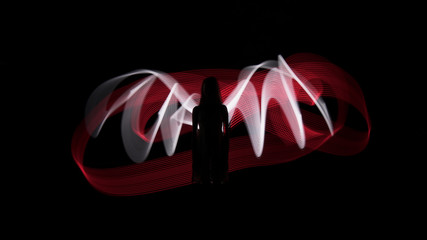 Woman silhouette against red and white backlight in shape of wings. Light painting photography. Long exposure.