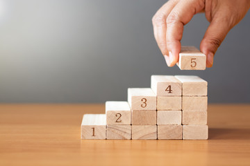 Women hand putting a wooden block on top and arranging wooden blocks stacking on wooden table. Wall mural