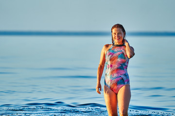 Portrait of a red-haired wet middle-aged woman in a swimsuit on a summer evening in the light of the setting sun.