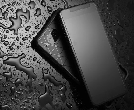 Smartphone with  protective cover on black background with water drops. Protect your smartphone from water.