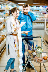 Young couple buying food standing with cart and long shopping list in the supermarket