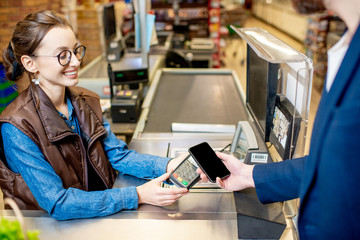 Man paying with a credit card for shopping at the cash register with cheerful cashier in the supermarket