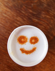 smiling face on cappuccino coffee takeaway, top view and space for text