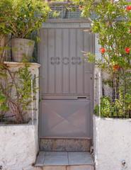 house entrance metallic gray door and flowers, Athens Greece, Anafiotika neighborhood