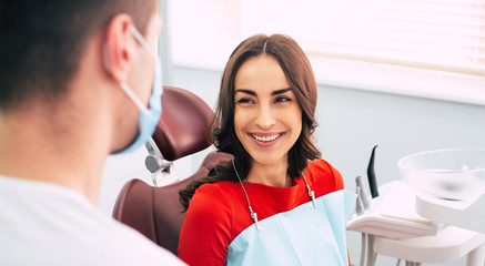 On the road to recovery. Bodacious girl in the dental chair next to the dentist with happy emotions because of the perfect work of the doctor in the dental center. Wall mural