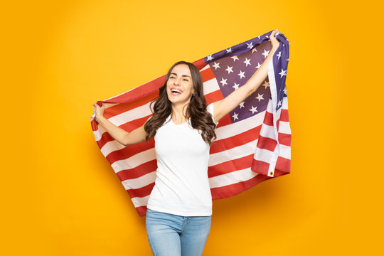 American dream.  Hilariously beautiful girl with long curly hair in denim jeans and white t-shirt is walking with the American flag in front of flaming yellow background.