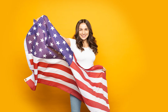 America's sweetheart. A girl full of exciting feelings in front of igneous yellow wall with American flag in her hands is ready to start her new life.