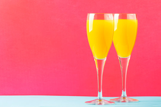 Festive alcohol cocktail mimosa with orange juice and cold dry champagne or sparkling wine in glasses, pink treandy background, place for text, selective focus