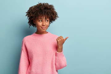 Isolated shot of cheerful lovely woman with Afro haircut, promots something aside, points thumb, looks away, wears oversized pink jumper, shows blank space over blue background. Advert concept.