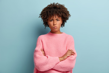 Picture of angry Afro American young woman looks with grumpy facial expression, keeps arms folded, displeased with latest result of work, poses over blue background, expresses dissatisfaction