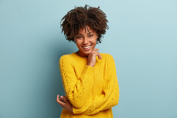 Charming amused happy woman with Afro haircut, keeps hands partly crossed over chest, has nice friendly conversation, wears yellow oversized sweater, isolated over blue background feels self satisfied