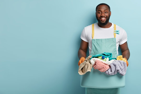 Photo of glad dark skinned housekeeper has toothy smile, white teeth, carries sorted clothes in basin or hamper, going to fasten o line with clothespins for drying, models over blue wall, empty space