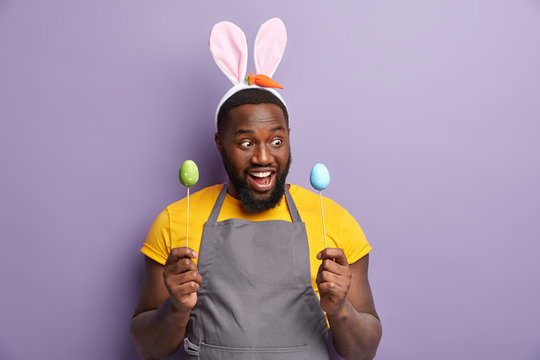 Happy surprised dark skinned stout man looks positively at painted eggs on sticks, has fun at home during Easter preparation, being bunny, models over lilac background. Festive food concept.