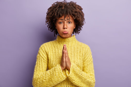 Unhappy woman pleads for forgiveness, keeps palms together, has regretful facial expression, believs God will help you to achieve desirable wish, wears yellow sweater, models over purple wall