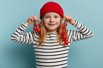 Lovely small girl collects homemade red ripe small tomatoes, takes fun with vegetables, eats organic food from greenhouse, wears stylish headgear and jumper. Healthy eating habits for kids concept