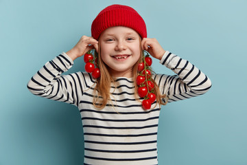 Glad pleasant looking small girl keeps branches of fresh red tomatoes near ears as if earrings, has fun while helps mother to cook dinner, dressed in striped clothes, models indoor. Childhood, eating