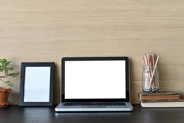 Workspace mockup laptop computer and office supply on office desk and wooden wall.