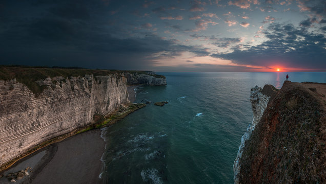 Panoramic view of a man standing on top of the cliffs at Etretat, France, at sunset.