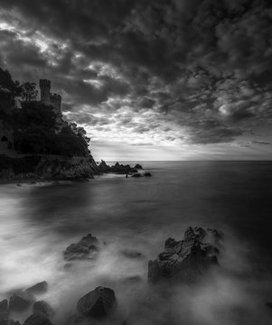 Black and white, long exposure capture of castle on a hill by the sea, Cala Frares, Lloret de Mar, Spain
