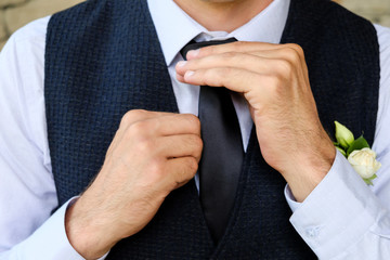 Man in a classic suit straightens his tie