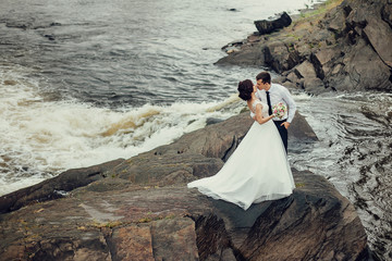 The bride in a luxurious white dress and a beautiful groom hugging against the background of nature. Newlyweds are on a rocky shore, around them the water is boiling