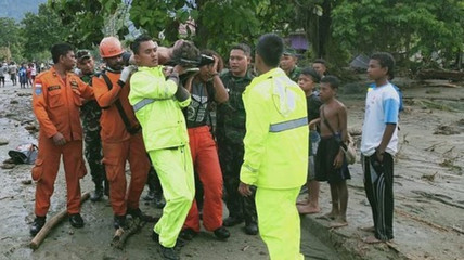 Search and Rescue crew members carry a person on a stretcher in Sentani