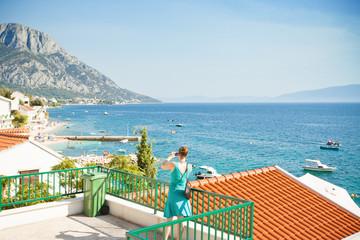 Brist, Dalmatia, Croatia - A woman taking a picture of the beautiful bay of Brist
