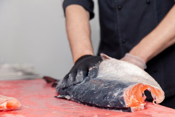 Closeup whole fresh salmon fish preparing fillet with knife on red cutting board in professional kitchen of restaurant. Concept Japanese food, sushi, sashimi, semi finished product, norwegian soup
