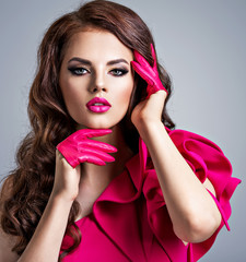 Fashionable woman in a red dress with a creative eye makeup.